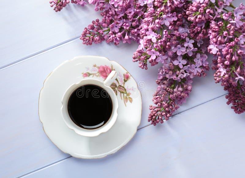 Φλιτζάνι του καφέ και κλάδοι της ανθίζοντας πασχαλιάς στον ξύλινο πίνακα στοκ φωτογραφία