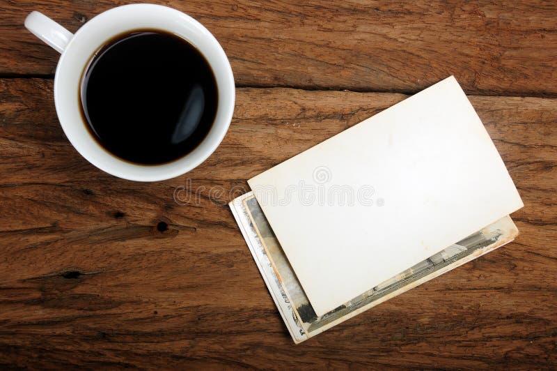 Φλιτζάνι του καφέ και παλαιό πλαίσιο φωτογραφιών εγγράφου στο ξύλινο υπόβαθρο στοκ εικόνες