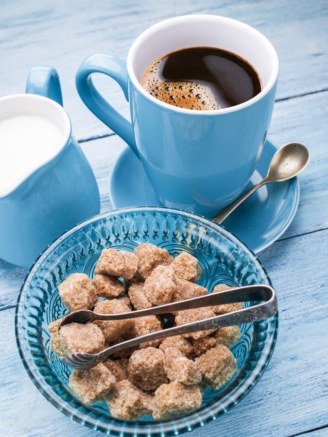 Φλιτζάνι του καφέ, κανάτα γάλακτος και κύβοι ζάχαρης καλάμων στοκ φωτογραφίες
