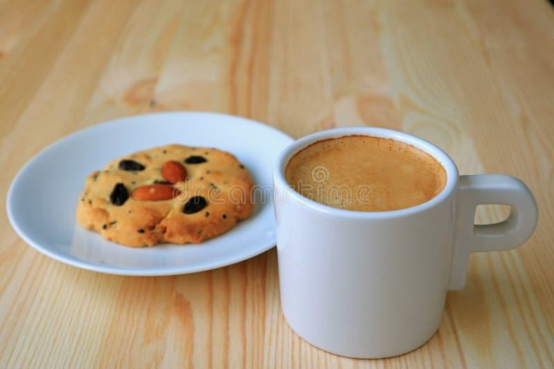 Φλιτζάνι του καφέ με ένα πιάτο του βουτύρου μπισκότου αμυγδάλων και σταφίδων στον ξύλινο πίνακα στοκ εικόνες με δικαίωμα ελεύθερης χρήσης