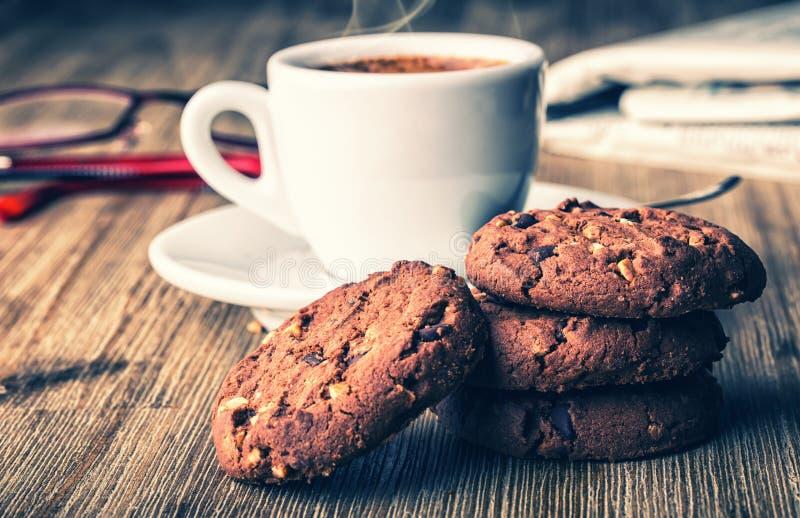 Φλιτζάνι του καφέ με τα μπισκότα μπισκότων και newspapper Μπισκότα μπισκότων σοκολάτας Μπισκότα σοκολάτας στην άσπρη πετσέτα λινο στοκ εικόνες