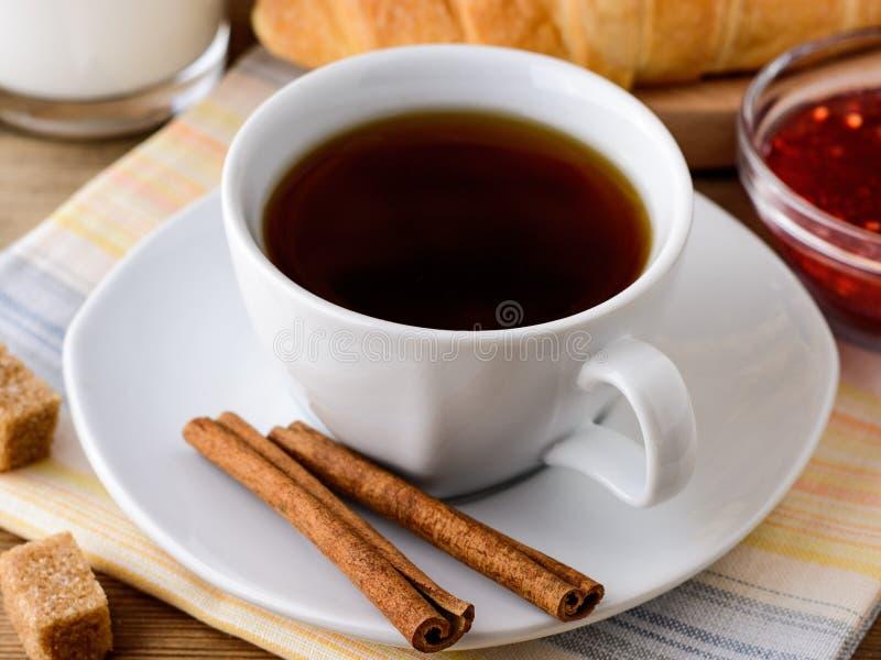 Φλιτζάνι του καφέ με τα ραβδιά κανέλας, καφετιά ζάχαρη και croissant στον ξύλινο πίνακα στοκ φωτογραφία με δικαίωμα ελεύθερης χρήσης