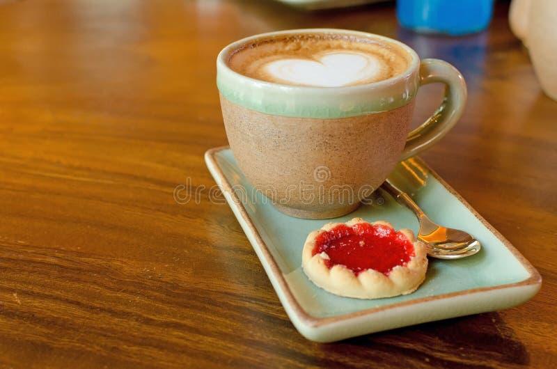 Φλιτζάνι του καφέ, μορφή καρδιών με το μπισκότο φραουλών στο ξύλο στοκ εικόνες