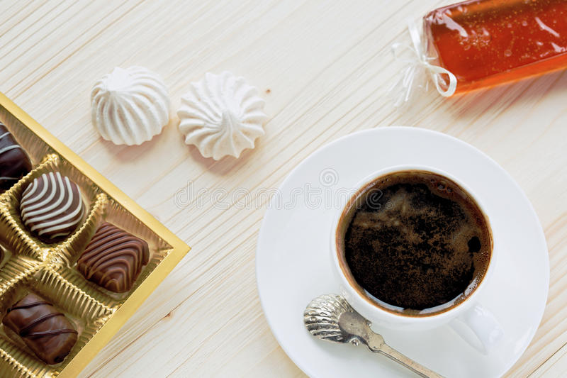 Φλιτζάνι του καφέ, σοκολάτες, μαρέγκα, ζελατίνα φρούτων χειροτεχνιών σε ένα ξύλινο υπόβαθρο στοκ φωτογραφία με δικαίωμα ελεύθερης χρήσης