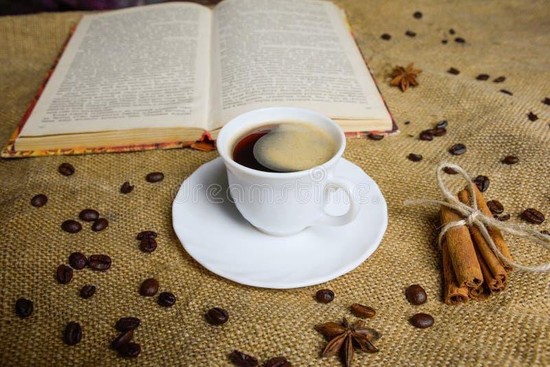 Φλιτζάνι του καφέ στο υπόβαθρο burlap με ένα βιβλίο απομονωμένη ιδανικό μακροεντολή καφέ προγευμάτων φασολιών πέρα από το λευκό ε στοκ φωτογραφία