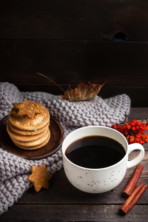 Φλιτζάνι του καφέ/τσάι, μπισκότα, πεσμένα φύλλα και μαντίλι στον ξύλινο πίνακα στοκ φωτογραφίες