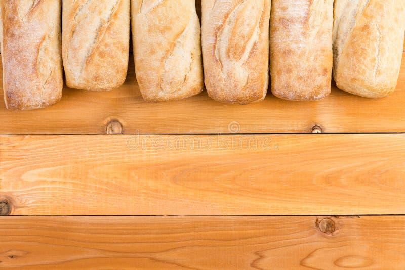 Φλοιώδη φρέσκα σύνορα φραντζολών ψωμιού στο ξύλο στοκ εικόνα με δικαίωμα ελεύθερης χρήσης