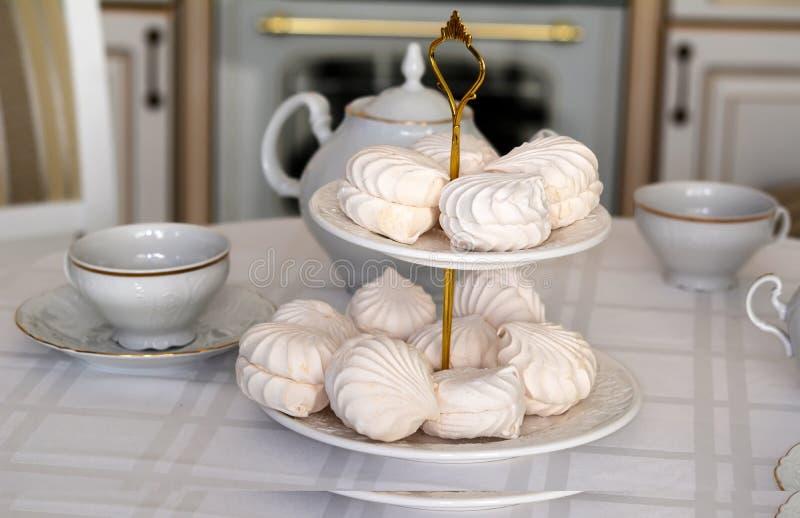 Φλυτζάνια και γλυκά στον πίνακα κουζινών στοκ φωτογραφίες με δικαίωμα ελεύθερης χρήσης