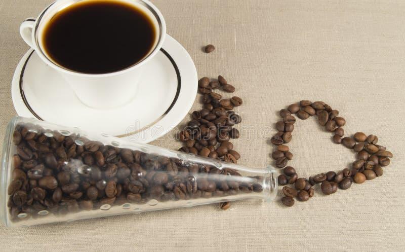 Φλυτζάνι και πιατάκι καφέ στο ύφασμα λινού Φασόλια καφέ στο μπουκάλι γυαλιού μορφής καρδιών στοκ εικόνα