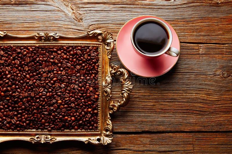 Φλυτζάνι και φασόλια καφέ στον εκλεκτής ποιότητας χρυσό δίσκο στοκ εικόνες