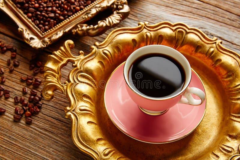 Φλυτζάνι και φασόλια καφέ στον εκλεκτής ποιότητας χρυσό δίσκο στοκ εικόνες με δικαίωμα ελεύθερης χρήσης
