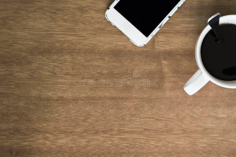 Φλυτζάνι και Smartphone καφέ στην ξύλινη άποψη υπολογιστών γραφείου στοκ εικόνα με δικαίωμα ελεύθερης χρήσης