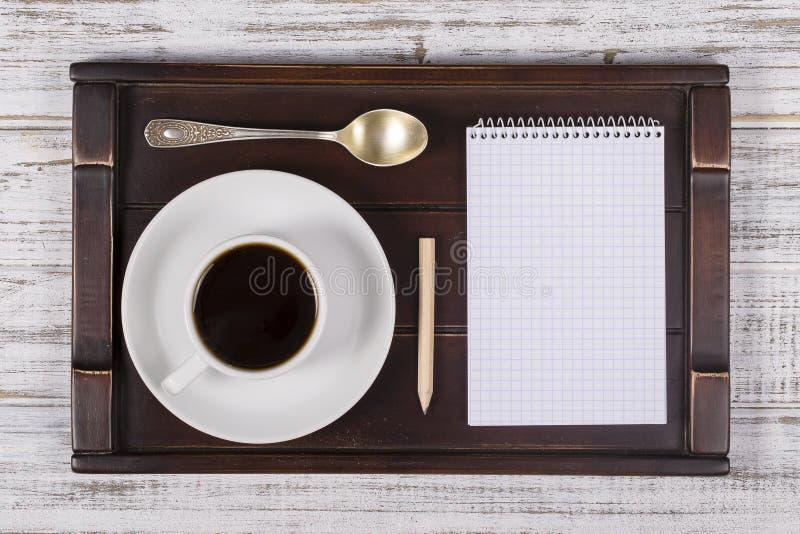 Φλυτζάνι καφέ με το βιβλίο σημειώσεων σε έναν δίσκο στον άσπρο ξύλινο πίνακα Έννοια τρόπου ζωής E στοκ φωτογραφίες με δικαίωμα ελεύθερης χρήσης