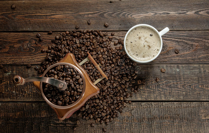 Φλυτζάνι καφέ με το μύλο και φασόλια στο σκοτεινό πίνακα Τοπ όψη στοκ εικόνα με δικαίωμα ελεύθερης χρήσης