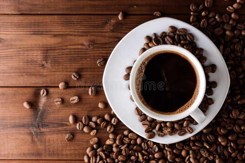 Φλυτζάνι καφέ με το πιατάκι και φασόλια στον ξύλινο πίνακα στοκ φωτογραφία με δικαίωμα ελεύθερης χρήσης