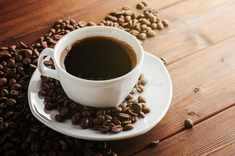 Φλυτζάνι καφέ με το πιατάκι και φασόλια στον ξύλινο πίνακα στοκ φωτογραφίες με δικαίωμα ελεύθερης χρήσης