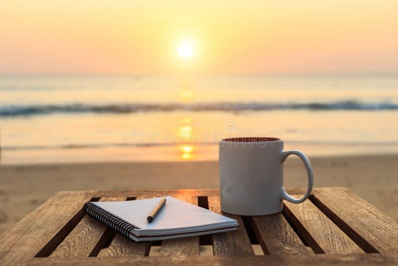 φλυτζάνι καφέ στον ξύλινο πίνακα στην παραλία ηλιοβασιλέματος ή ανατολής στοκ εικόνες με δικαίωμα ελεύθερης χρήσης