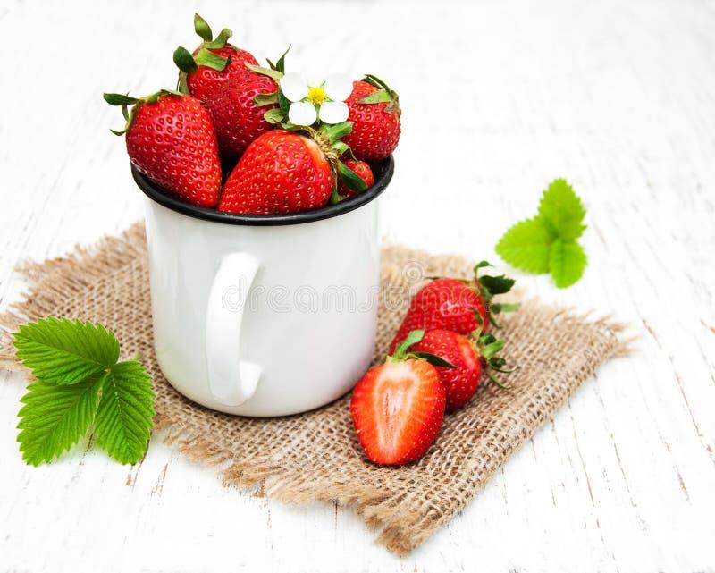 Φλυτζάνι μετάλλων με τις φράουλες στοκ εικόνα