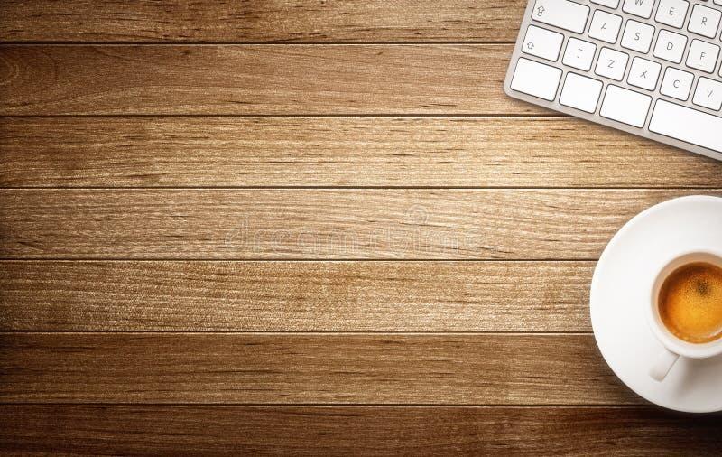 Φλυτζάνι πληκτρολογίων και καφέ στο ξύλινο υπόβαθρο στοκ φωτογραφία