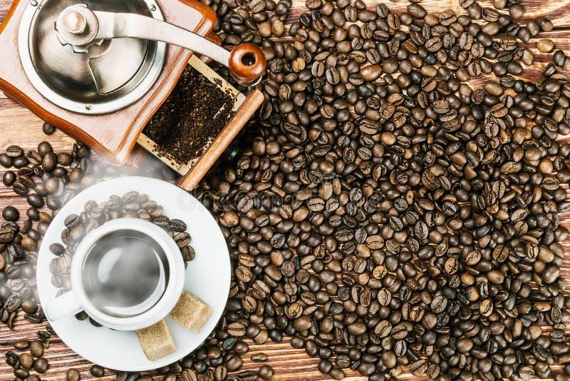 Φλυτζάνι του θερμών καφέ και του μύλου σε έναν ξύλινο πίνακα στοκ φωτογραφίες