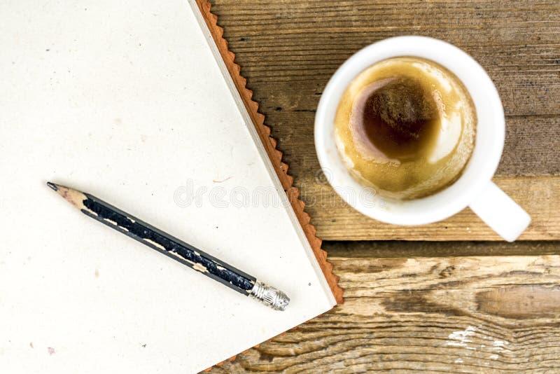 Φλυτζάνι του ισχυρού καφέ με ένα μολύβι και ένα σημειωματάριο στοκ φωτογραφίες με δικαίωμα ελεύθερης χρήσης