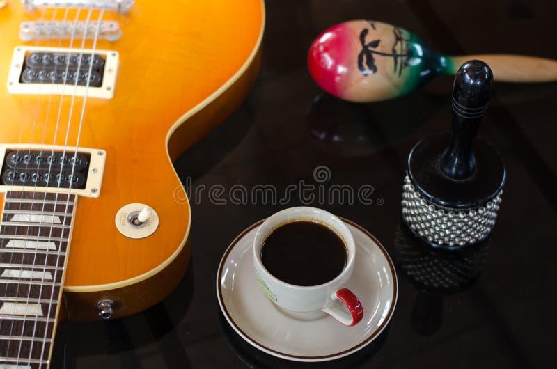 Φλυτζάνι του καυτού καφέ στη μουσική στο μαύρο υπόβαθρο στοκ εικόνα