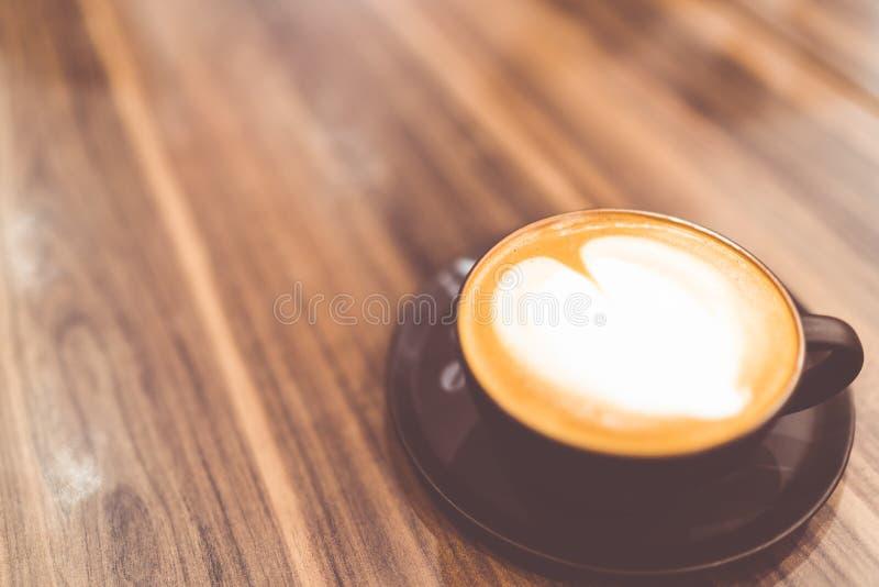 Φλυτζάνι του καυτού καφέ cappuccino με διαμορφωμένη την καρδιά latte κτυπημένη τέχνη κρέμα στον εκλεκτής ποιότητας τόνο, διάστημα στοκ εικόνα