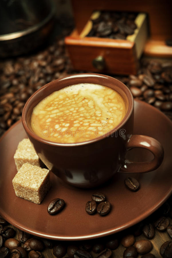 Φλυτζάνι του μαύρου καφέ με τη ζάχαρη στο υπόβαθρο των φασολιών καφέ στοκ φωτογραφία με δικαίωμα ελεύθερης χρήσης