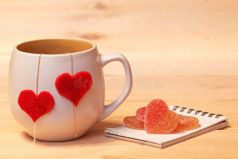 Φλυτζάνι του τσαγιού με τις καρδιές και τη ζελατίνα γλασαρισμένων φρούτων στοκ εικόνες με δικαίωμα ελεύθερης χρήσης