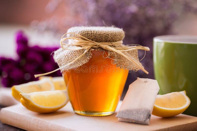 Φλυτζάνι του τσαγιού με το υπόβαθρο μελιού και λεμονιών στοκ φωτογραφία