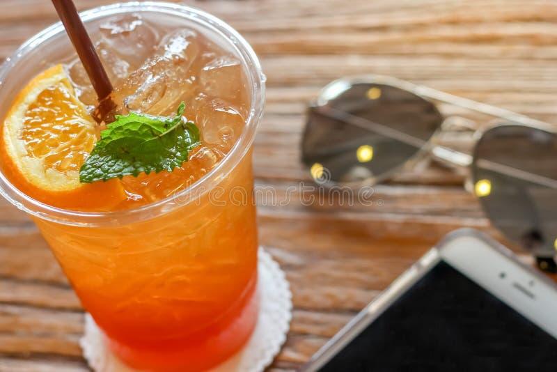 Φλυτζάνι του τσαγιού πάγου λεμονιών με το πορτοκάλι και της μέντας στην κορυφή στο καφετί υπόβαθρο σύστασης φλοιών όμορφο με το θ στοκ φωτογραφία με δικαίωμα ελεύθερης χρήσης