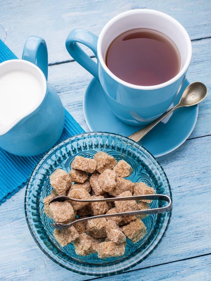 Φλυτζάνι του τσαγιού, της κανάτας γάλακτος και των κύβων ζάχαρης καλάμων στοκ εικόνα