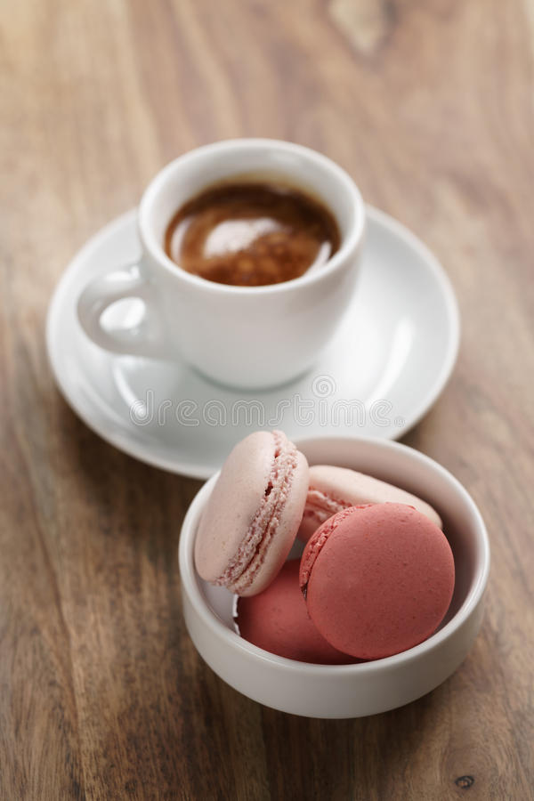 Φλυτζάνι του φρέσκου espresso με τα macarons στον ξύλινο πίνακα στοκ εικόνα