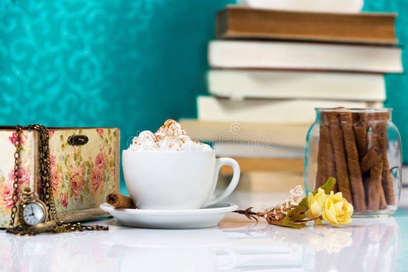 Φλυτζάνι του cappuccino με τους ρόλους και τα βιβλία σοκολάτας στο υπόβαθρο στοκ φωτογραφίες με δικαίωμα ελεύθερης χρήσης