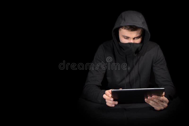Χάκερ με το PC ταμπλετών που αρχίζει cyber την επίθεση, στο Μαύρο στοκ φωτογραφίες