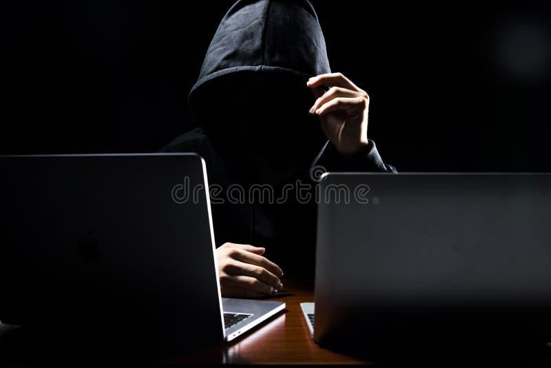 Χάκερ μπροστά από τον υπολογιστή του σκοτεινό πρόσωπο στοκ εικόνα