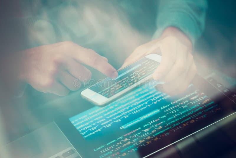 Χάκερ που χρησιμοποιεί τον υπολογιστή, το smartphone και την κωδικοποίηση για να κλέψει τον κωδικό πρόσβασης α στοκ φωτογραφίες