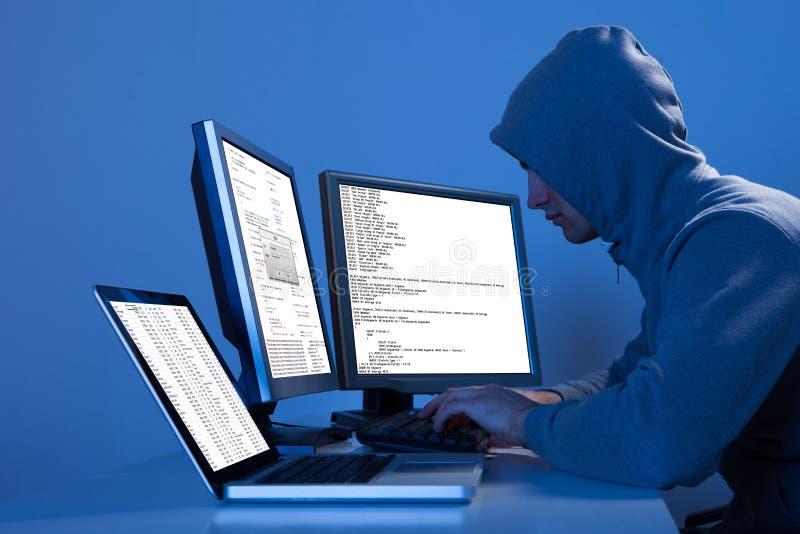 Χάκερ που χρησιμοποιεί τους πολλαπλάσιους υπολογιστές για να κλέψει τα στοιχεία στοκ φωτογραφίες