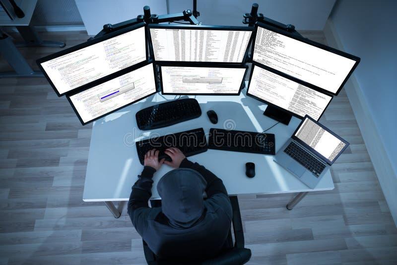 Χάκερ που χρησιμοποιεί τους υπολογιστές για να κλέψει τα στοιχεία στοκ φωτογραφίες
