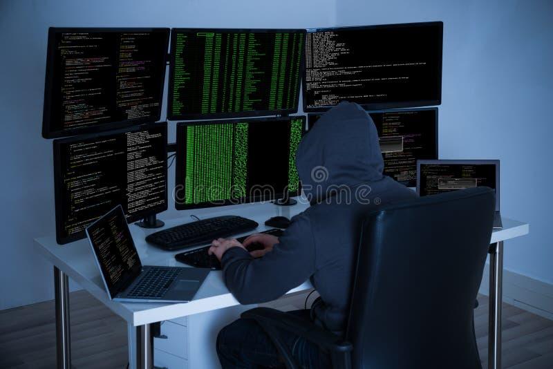 Χάκερ που χρησιμοποιεί τους υπολογιστές για να κλέψει τα στοιχεία στοκ εικόνες