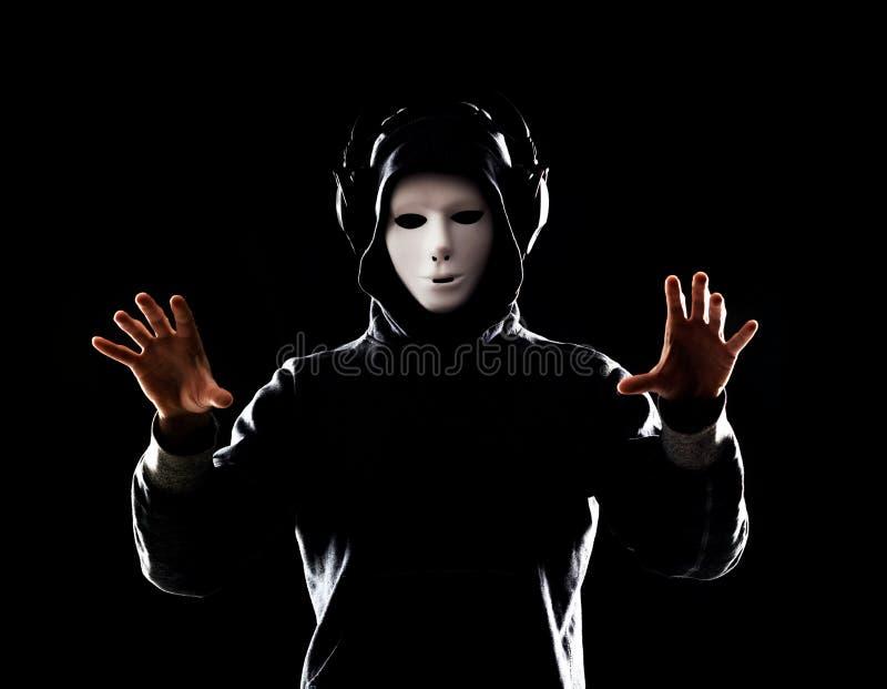 Χάκερ υπολογιστών στην άσπρη μάσκα και hoodie Κρυμμένο σκοτεινό πρόσωπο Κλέφτης στοιχείων, απάτη Διαδικτύου, darknet και cyber ασ στοκ εικόνες με δικαίωμα ελεύθερης χρήσης