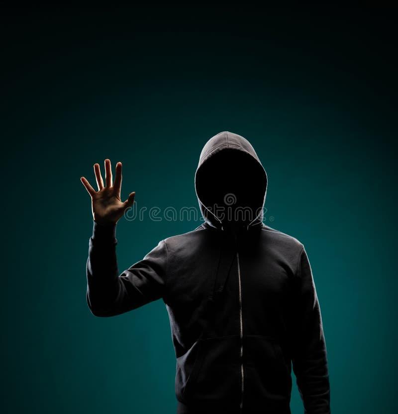 Χάκερ υπολογιστών στο hoodie Κρυμμένο σκοτεινό πρόσωπο Κλέφτης στοιχείων, απάτη Διαδικτύου, darknet και cyber έννοια ασφάλειας στοκ φωτογραφία