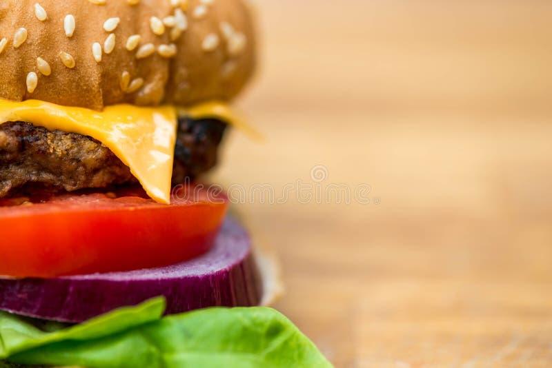 Χάμπουργκερ ή Beefburger λιβρών τετάρτων σε ένα κουλούρι ψωμιού σουσαμιού στοκ εικόνα