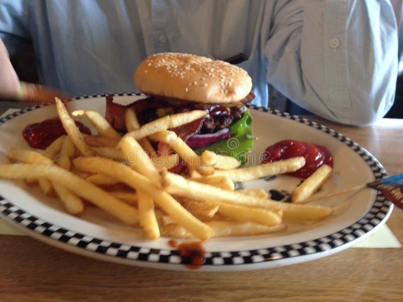 Χάμπουργκερ και τηγανητά στο γευματίζοντα στοκ εικόνες με δικαίωμα ελεύθερης χρήσης