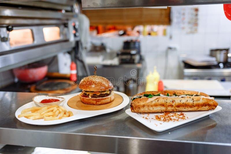 Χάμπουργκερ και baguette με το σολομό στα πιάτα στοκ εικόνες με δικαίωμα ελεύθερης χρήσης