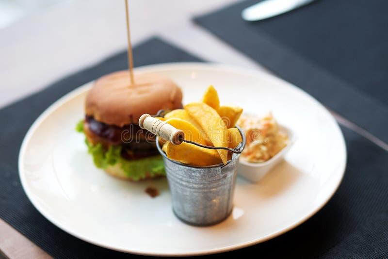 Χάμπουργκερ με τα τηγανητά στο άσπρο πιάτο στοκ εικόνες με δικαίωμα ελεύθερης χρήσης
