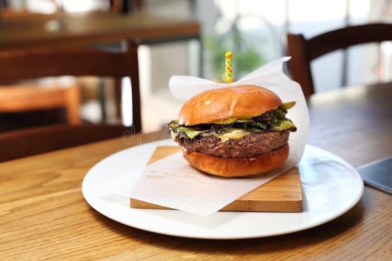 Χάμπουργκερ με το τυρί και τα πράσινες λαχανικά και τη σαλάτα στοκ εικόνα