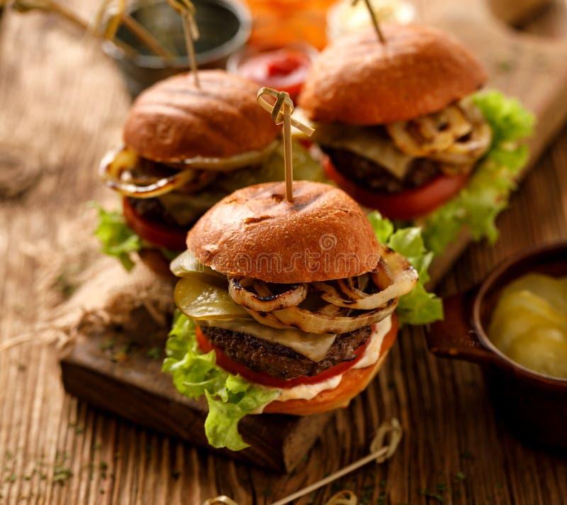 Χάμπουργκερ, σπιτικά burgers με τα ψημένα στη σχάρα κουλούρια με την προσθήκη της προσθήκης cutlet βόειου κρέατος, μαρούλι, ντομά στοκ φωτογραφίες