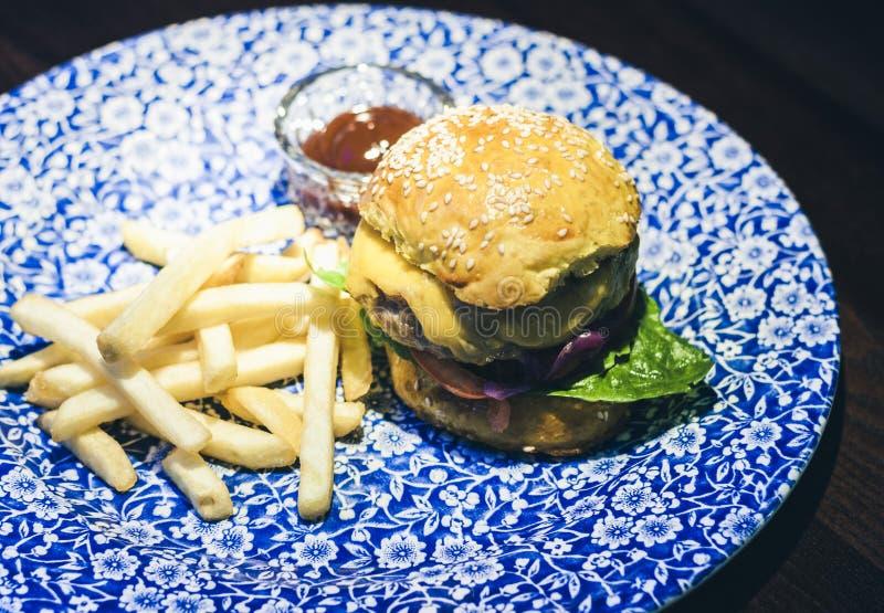 Χάμπουργκερ, τηγανητά και σάλτσα κοτόπουλου στο μπλε πιάτο στο εστιατόριο στοκ φωτογραφία με δικαίωμα ελεύθερης χρήσης