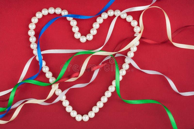 Χάντρες υπό μορφή καρδιάς και πολύχρωμων κορδελλών σατέν στοκ φωτογραφία με δικαίωμα ελεύθερης χρήσης